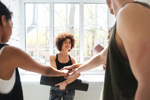 Group of healthy pretty people making team gesture while doing yoga in gym