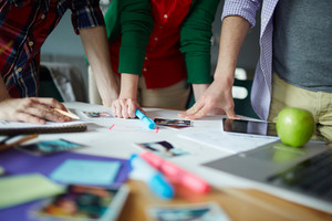 Group of human hands on workplace with design supplies