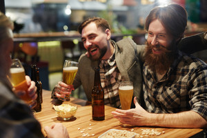 Group of men drinking beer and having talk in pub