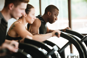 Group of multiracial young women and men exercising on a treadmill at the gym