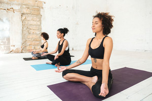 Group of women sitting on a yoga mats and meditating with eyes closed in a studio