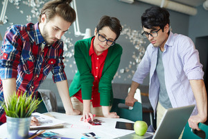 Group of young creative people wearing casual clothes collaborating at meeting in office standing round table and looking at photographs and documents
