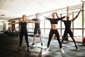 Group of young fit people doing sport exercises together at the gym