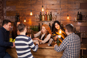 Group Of Young Friends Relaxing In Bar Standing At Counter. Hipster pub.