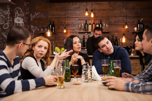 Group of young friends sitting around table in bar togethe. Cheerful mood.