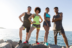 Group of young healthy cinfident sports people standing and looking at camera outdoors
