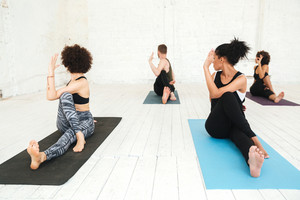 Group of young healthy people wearing tracksuits doing yoga in gym and sitting on training mats