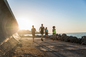 Group of young sporty friends jogging together outdoors at the beach