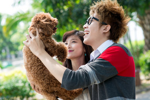 Guy holding a poodle and laughing