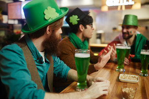 Guys in green hats relaxing in pub and having beer