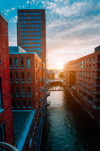 HafenCity. Bridge over canal and red brick buildings in the old warehouse district Speicherstadt in Hamburg in golden hour sunset light, Germany. View from above