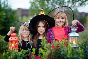 Halloween girls with lanterns looking at camera in garden