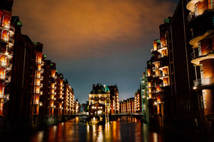 Hamburg, Germany. View of Wandrahmsfleet at dusk illumination light with clouds above. Located in Warehouse District - Speicherstadt Landmark of HafenCity quarter. Most visited touristic famous place