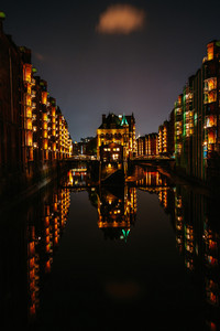 Hamburg, Germany. View of Wandrahmsfleet at dusk illumination light with reflection in the water. Located in Warehouse District - Speicherstadt Landmark of HafenCity quarter.
