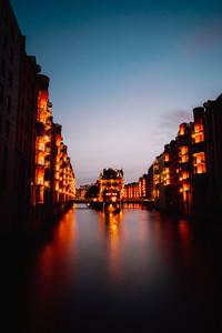 Hamburg, Germany. View of Wandrahmsfleet during sunset with illuminated buildings. Warehouse Landmark District - Speicherstadt of HafenCity quarter. Most visited touristic famous place