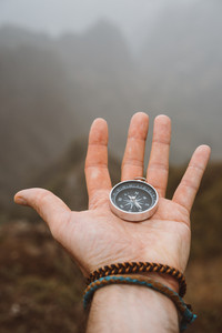 Hand holding a compass. Silhouette of monumental mountain formation in background