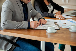 Hand of businessman signing a contract in the meeting room. Close up image