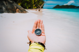 Hand with compass against tropical sandy beach and ocean. POV Travel concept