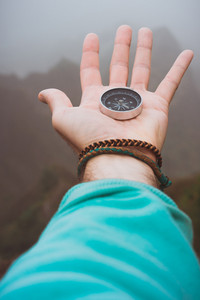 Hand with compass on the rock in front of the monumental mountain range silhouette in the fog