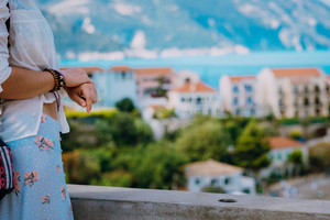 Hands crop close up. Tourist woman enjoying view of colorful tranquil village Assos on sunny day. Kefalonia, Greece
