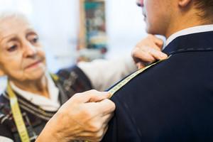 Hands of fashionist with tape measuring jacket shoulder length