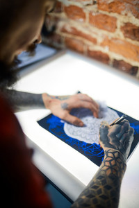 Hands of man with tattooes drawing ornament with pen