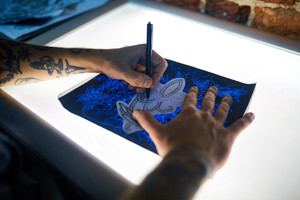 Hands of tattooer drawing picture of new creative adorment