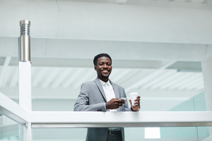 Handsome African American manager looking at camera with toothy smile while standing at spacious office lobby with smartphone and paper cup of coffee in hands, portrait shot