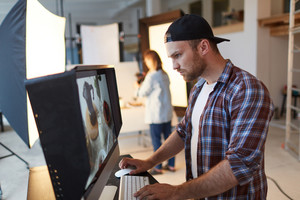 Handsome bearded food designer standing in front of computer monitor and looking through photos, interior of spacious production studio on background