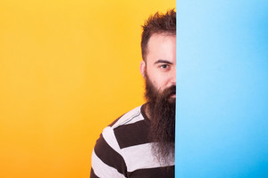 Handsome bearded hipster hiding behind a blue panel over yellow background. Looking at the camera. Cool t-shirt.