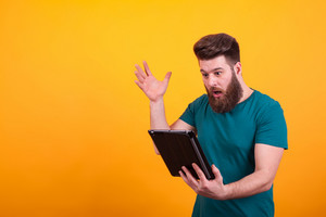 Handsome bearded man in green t-shirt looking shocked at tablet over yellow background. Cool hipster man.