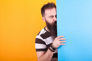 Handsome bearded man looking at a blue copy space over yellow background. Cool t-shirt. Stripped t-shirt.