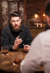 Handsome bearded man looking at his friend and shuffle cards. Men lifestyle. Rich men.