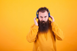 Handsome bearded man looking at the camera and listening music on blue headphones over yellow background. Cool song. Yellow hoodie.