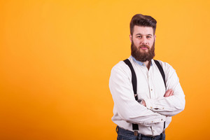 Handsome bearded man with his arms crossed looking serious at the camera over yellow background. Hipster man . Stylish man.