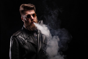 Handsome bearded man with leather jacket wearing cool glasses over black background. Attractive man. Sexy man.