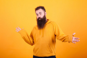 Handsome bearded man with orange hoodie looking confused. over yellow background. Stylish man. Cool beard.