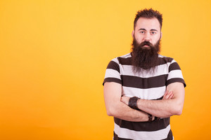Handsome bearded man with stripped t-shirt holding arms crossed and looking at the camera over yellow background. Casual style. Cool beard.