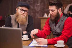 Handsome bearded men having business video call on their laptop in a coffee shop. Coffee cup. Laptop. Successful men.