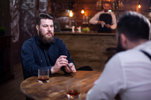 Handsome bearded men playing card in a pub and drinking whiskey. Attractive men. Stylish beard