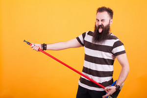 Handsome bearded young man picking up a broom as if it was a guitar over yellow background. Handsome man. Playing guitar,.