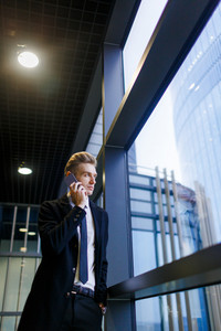 Handsome blond-haired entrepreneur talking to his business partner on smartphone while looking out window of office lobby, portrait shot