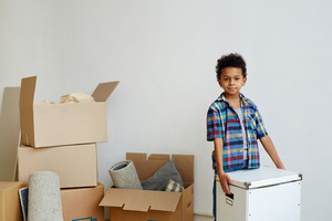 Handsome child with box helping during home renovation