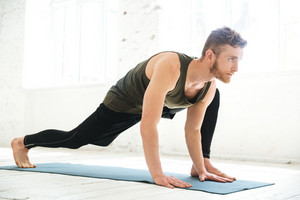 Handsome concentrated man doing yoga on mat in the studio