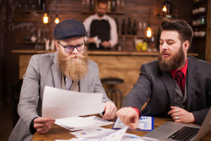 Handsome coworkers reading documents in a coffee shop. Succesful men. Men in suit. Bearded men.