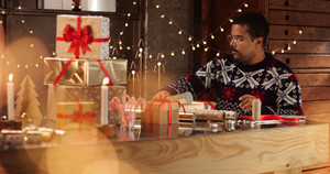 Handsome dark skinned man in black white and red fairisle sweather wrapping Christmas present among decorations and lights