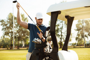 Handsome male golfer taking clubs from a bag in a golf cart at the green course