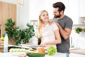 Handsome man cooking with his girlfriend at home in the kitchen