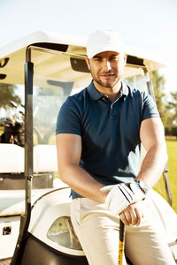 Handsome young male golfer with club resting while leaning on a cart