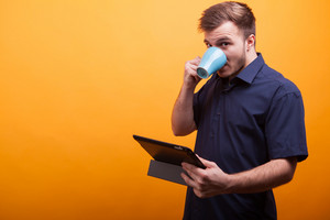Handsome young man looking at tablet computer and drinking coffee over yellow background. Enjoying coffee